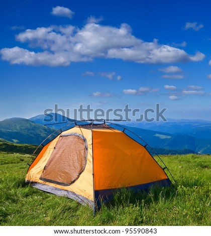 orange touristic tent in a mountains - stock photo