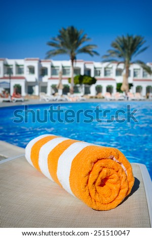 orange towel on a sun lounger on the background of the pool. - stock photo