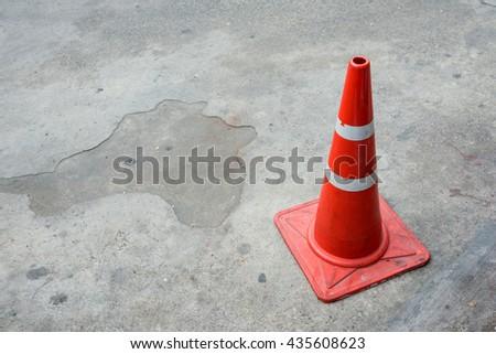 Orange Traffic Cone on gray cement - stock photo