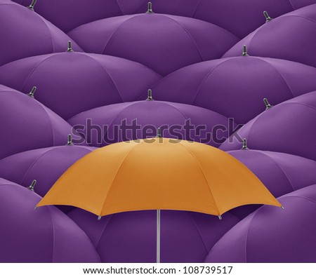 Orange umbrella Stand out of a crowd, individuality and unique - stock photo