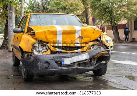 Orange vehicle wrecked in horrific car crash, dragged on sidewalk - stock photo