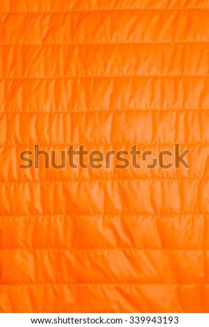 orange warm insulated texture of jacket,warm light weight  insulated  jacket  on white background. - stock photo