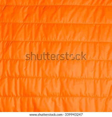 orange warm insulated texture of jacket,warm light weight  insulated  jacket  on white background,Ready for product display montage.  - stock photo