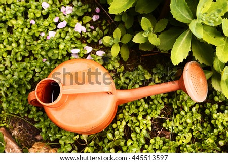 orange water can on the green garden background - stock photo