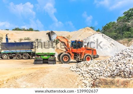 orange wheel loader loading gravel rock at gravel pit against blue sky. - stock photo