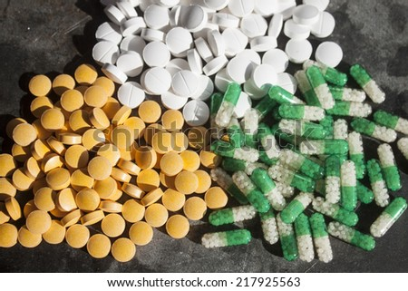 Orange, white and green vitamins and supplements - stock photo