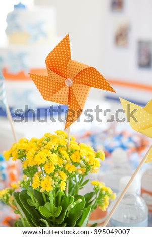 Orange windmill toy and yellow roses on birthday party - stock photo