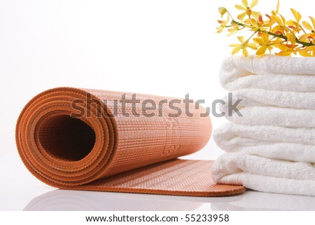 orange yoga mat, towel and orchid with reflex - stock photo