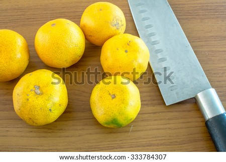 Oranges and a squeezer on wooden table with knife  - stock photo