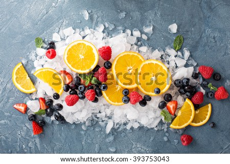 Oranges and berries on ice making summer refreshments - stock photo