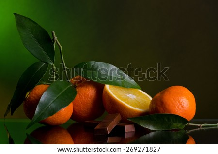 Oranges and Chocolate on dark green background - stock photo