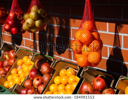 Oranges, grapefruits, apples and pomegranates at the  fresh juice stall in Jaffa (Israel). Contrast of bright sunshine and dark shadows. Selective focus on the oranges in mesh bag at the right. - stock photo