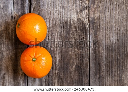 oranges on textured weathered wooden table - top view - stock photo