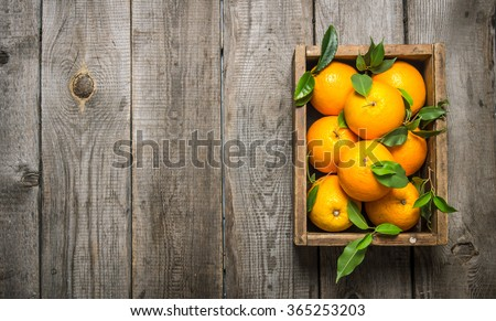 Oranges with leaves in an old box. On a wooden table. Free space for text . Top view - stock photo