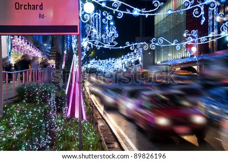Orchard Road, Singapore. The street and buildings with lights and decorative items in preparation for Christmas. motion blurred - stock photo
