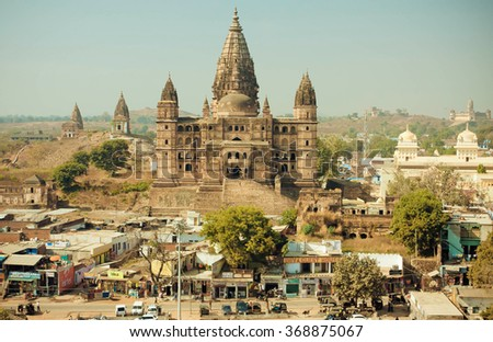 ORCHHA, INDIA - DEC 21: Busy city streets and tall hindu Chaturbhuj Temple on December 21, 2012. Chaturbhuj Temple dedicated to Vishnu, built in 16th century in Madhya Pradesh state - stock photo