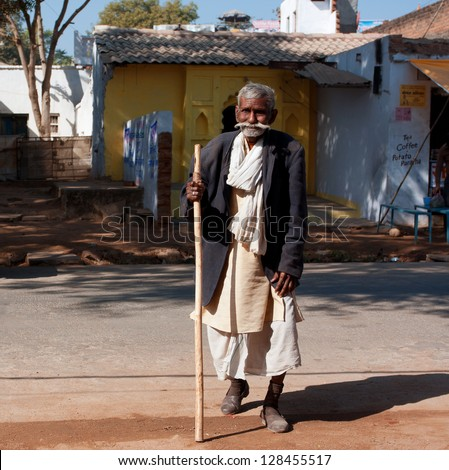 ORCHHA, INDIA - DEC 20: Poor elderly man walk the street at the sunny day on December 20 2012, in Orchha, India.  60-plus age group in India will increase to 100 million people in 2013. - stock photo