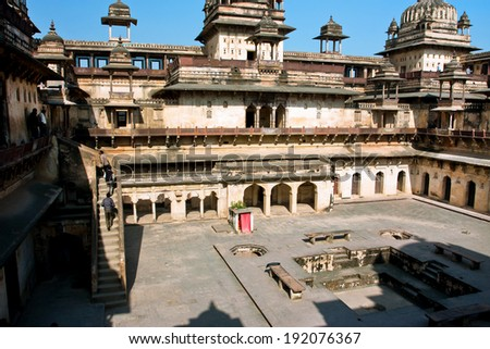ORCHHA, INDIA - DEC 21: Tourists climb the stone stairs of the ancient structure of Citadel of Jahangir on December 21, 2012. Fort Jahangir Mahal built in 1598. Its classical Mughal Architecture - stock photo