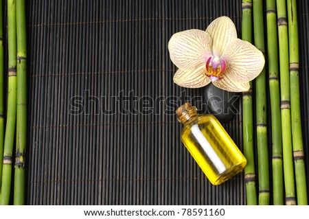 orchid with thin grove and stones on mat - stock photo