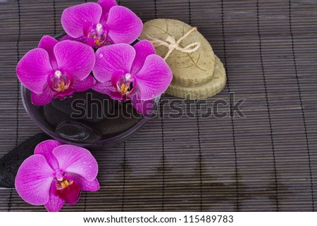 orchids  and spa settings on black  bamboo mat - stock photo