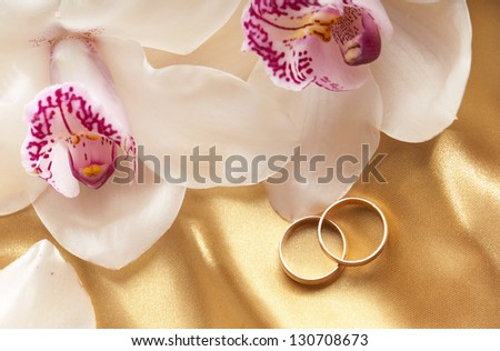 orchids on a golden background and couple of wedding rings - stock photo