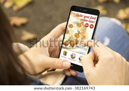 order food concept: woman holding a 3d generated smartphone ordering fast food. Graphics on screen are made up. - stock photo
