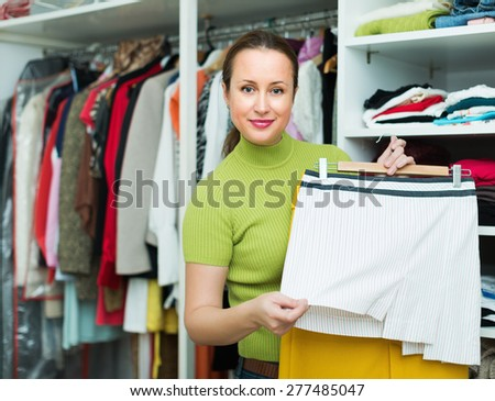 Orderly happy housewife arranging clothes at wardrobe indoor - stock photo