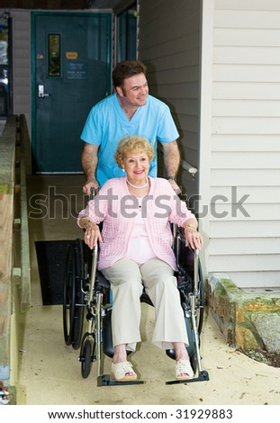 Orderly takes a disabled senior woman out for a walk. - stock photo