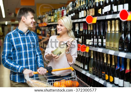 Ordinary family buying bottle of wine at food shop - stock photo