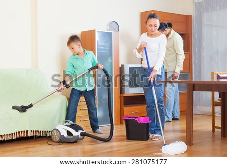 Ordinary family of three with teenager doing housework together in home - stock photo