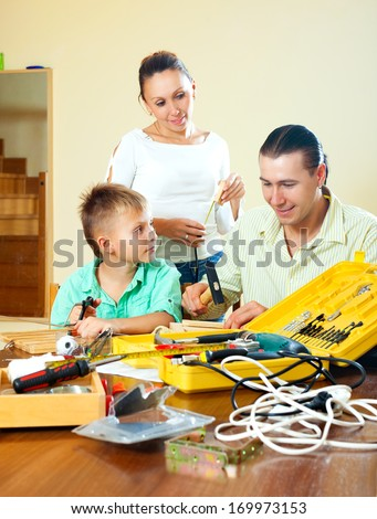 Ordinary nice family of three making something with tools at home  - stock photo