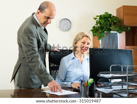 Ordinary office scene with two elderly and serious co-workers - stock photo