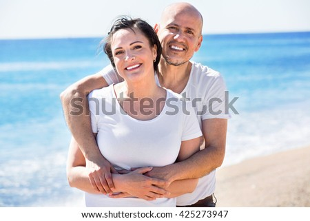 Ordinary positive  mature couple gladly hugging each other and enjoying the beach - stock photo