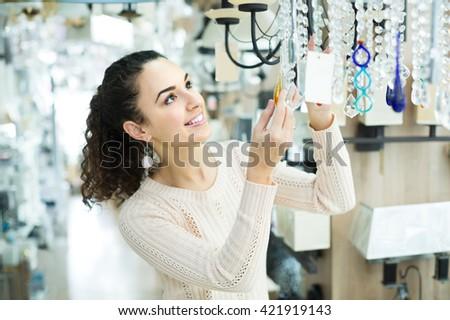 Ordinary spanish woman doing shopping in lighting shop - stock photo