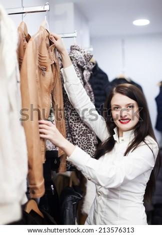 Ordinary woman choosing jacket at clothing store - stock photo