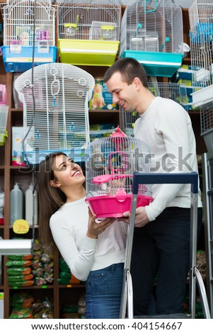Ordinary young couple buying cage for bird in shop - stock photo