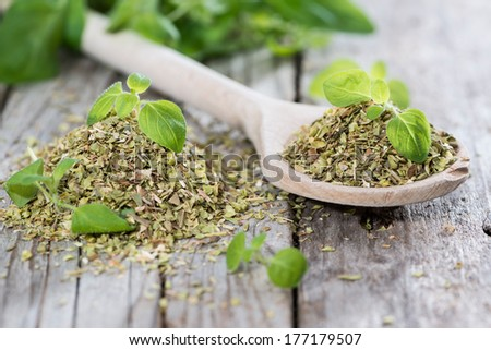 Oregano on a wooden spoon (against wooden background) - stock photo