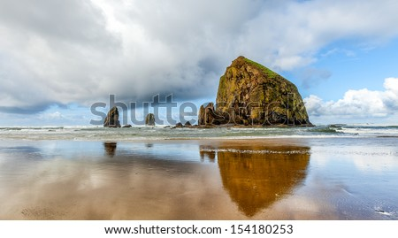 Oregon coast scenic Haystack Rock on a dramatic day with clouds and reflections. Famous destination for bird watchers. - stock photo