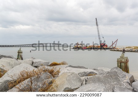 Oregon Inlet on the Outer Banks of North Carolina. Dredge clearing the inlet and a wading fisherman fishing. Bonner bridge in background - stock photo