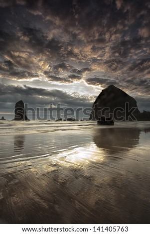 Oregon's Cannon Beach and the iconic Haystack Rock at sunset - stock photo