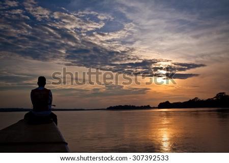 ORELLANA, ECUADOR - AUGUST 13, 2012: Unidentified tourist in a canoe contemplating stunning rainforest sunset, Yasuni National Park, Ecuador - stock photo
