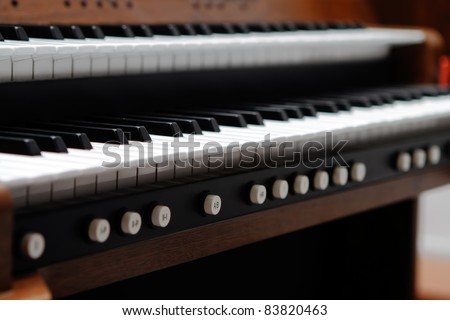 Organ keyboard in catholic church, focus on the fifth round button A/B from left side under the keyboard - stock photo