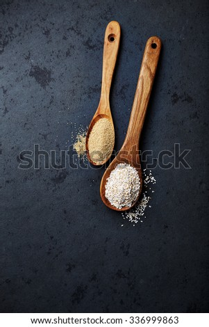 Organic amaranth on wooden spoons (whole and puffed)  - stock photo