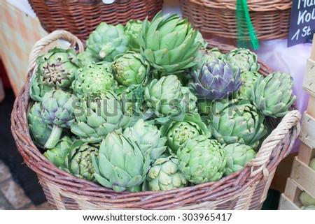 organic artichoke in a basket on farmers market  - stock photo