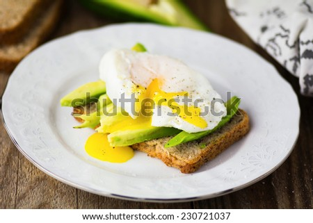 Organic avocado and poached egg on whole wheat toasted bread - stock photo