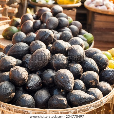 Organic avocado for sale at outdoor asian marketplace. Food background - stock photo