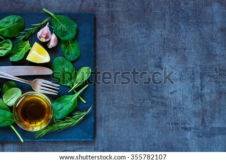 Organic baby spinach leaves and olive oil on dark slate background, top view. Healthy food, diet or cooking concept. - stock photo