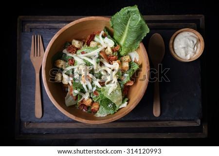 Organic caesar salad in wodden bowl with caesar dressing. International food. - stock photo