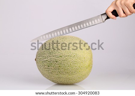 Organic Cantaloupe melon fruit with kitchen knife in hand isolated on white background - stock photo