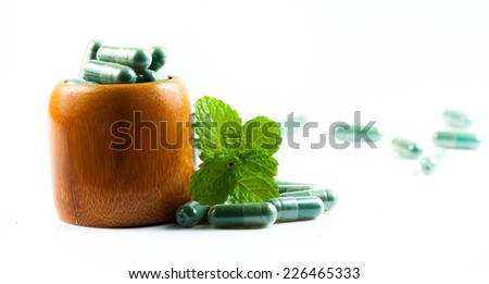 Organic capsule with mint leaves - stock photo